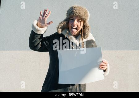 Drôle jeune fille de l'adolescence dans des vêtements d'hiver, hat montrant nettoyer feuille de papier blanc. Banque D'Images