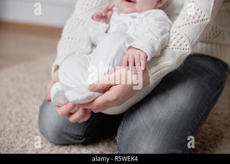 Close up. bébé dans les bras d'une mère aimante Banque D'Images