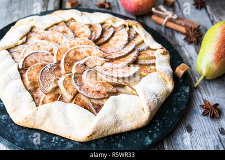 Tourte aux pommes, poires et cannelle sur un vieux fond de bois Banque D'Images