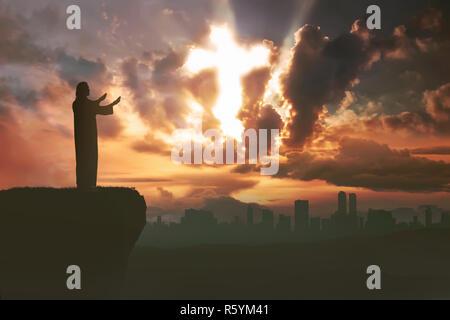 Silhouette of man à prier Dieu avec rayon de lumière façonner cross Banque D'Images