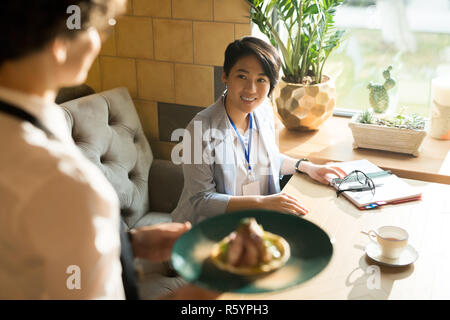 Cheerful woman smiling at serveuse avec sa lave Banque D'Images