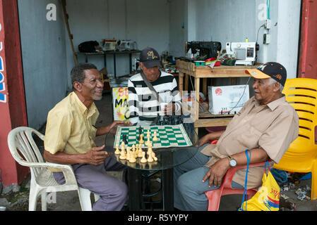 Les hommes jouant aux échecs à l'extérieur d'un atelier de réparation de machines à coudre. Vie quotidienne à Cartagena de Indias, Colombie. Oct 2018