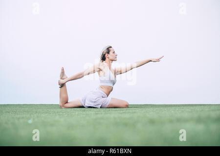 Très belle jeune fille blonde faire pilates yoga position équilibrée à la piscine dans le jardin sur le tapis - un minimum de pose pour la construction du corps parfait wit Banque D'Images