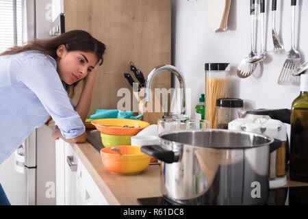 Femme debout près de l'évier de cuisine à la recherche d'ustensiles à Banque D'Images