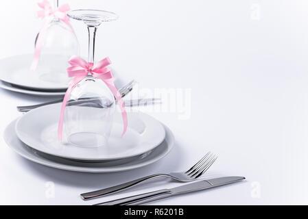 Verres à vin à l'envers avec décoration rose comme fond pour l'invitation et menu Banque D'Images