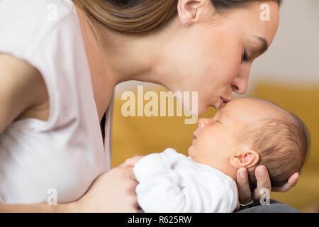 Loving Mother Cuddling Baby Son et lui donner des baiser sur le front