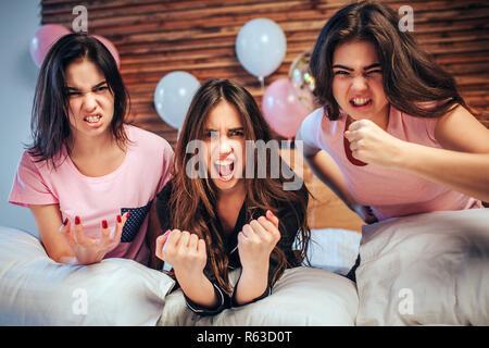 Les jeunes femmes émotionnelle regard sur appareil photo. Ils s'asseoir sur le lit avec faces en colère. Les filles sont très émotionnel Banque D'Images