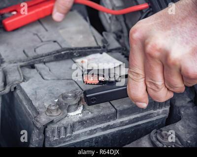 Homme de recharger une batterie de voiture morte en hiver en