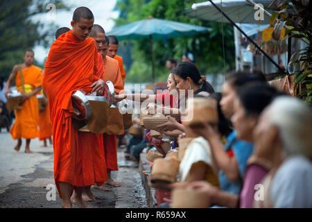 Tak bat - rituel des moines bouddhistes recevoir le riz et de la nourriture de pupulation tôt le matin à Luang Prabang, Laos, Asie Banque D'Images