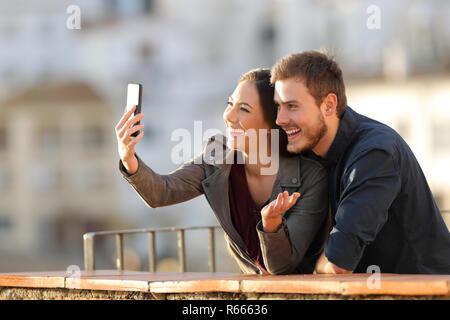 Heureux couple ayant un appel vidéo ou prendre des autoportraits avec un téléphone intelligent à un balcon au coucher du soleil