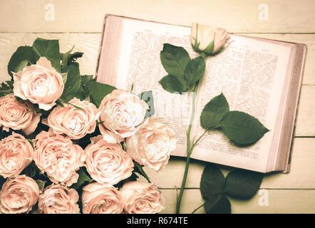 Bouquet de roses et un livre ouvert dans le style rétro Banque D'Images