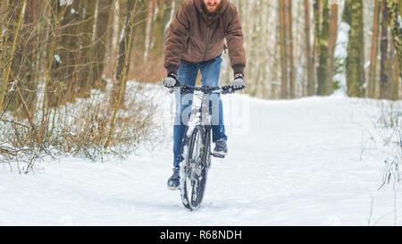 L'équitation cycliste VTT en forêt d'hiver. Montée à cheval sur mtb Banque D'Images