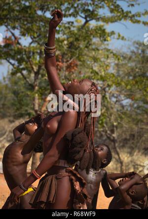 Tribu Himba jeune femme regardant un drone dans le ciel, la province de Cunene, Oncocua, Angola