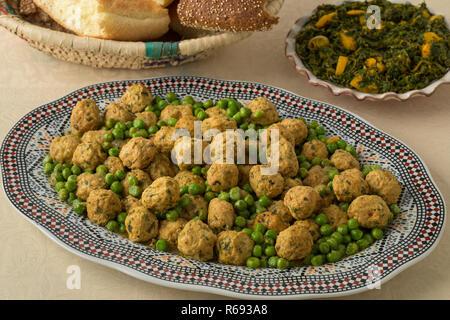 Avec le plat de poulet hachée de style marocain et boules de pois verts, salade d'épinards et de pain Banque D'Images