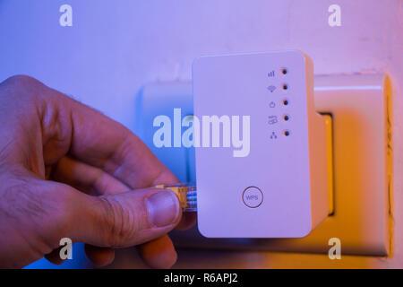 Insérer le câble Ethernet à l'homme WiFi Extender dispositif qui est en prise électrique sur le mur Banque D'Images
