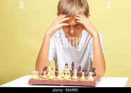 Enfant jouant aux échecs. Garçon à la recherche au conseil d'échecs et de réfléchir à sa stratégie.
