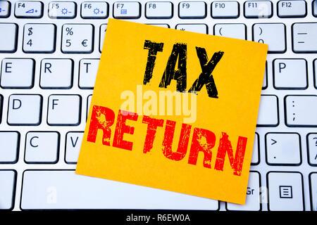 Déclaration d'impôt. Concept d'affaires pour l'argent de comptabilité écrite Retour sur sticky note sur le clavier blanc arrière-plan. Banque D'Images