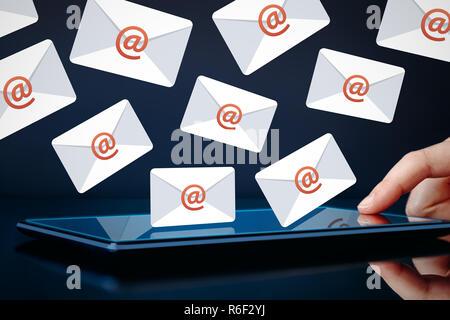 Newsletter et email marketing concept. Hand touching tablet montrant des icônes d'e-mail sur fond sombre. Banque D'Images