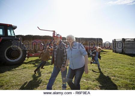 Couple Senior farmer et petits-fils en champ ensoleillé Banque D'Images