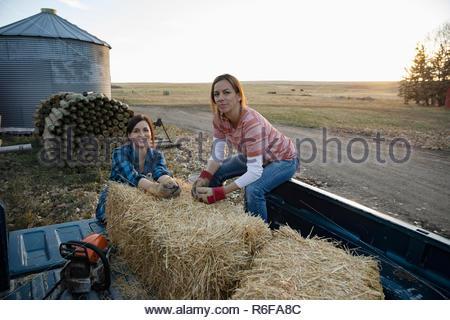 Portrait confiant de paysannes avec des balles de foin sur pickup truck on farm Banque D'Images