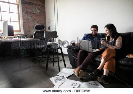 Les gens d'affaires créatrices de boire du café et à l'aide de l'ordinateur portable sur canapé bureau Banque D'Images