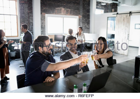 Creative business people toasting beer glasses in bureau loft Banque D'Images