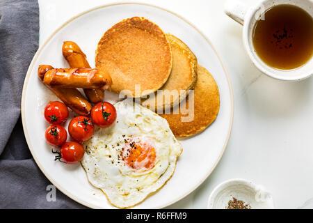 L'avoine banane crêpes avec saucisses, œufs frits et tomates cerises Banque D'Images