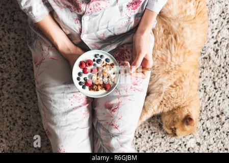 Girl eating healthy breakfast bowl avec yogourt et petits fruits. Régime Végétarien, petit-déj. Vue d'en haut