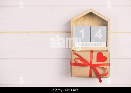 Calendrier Cube avec coeur rouge et boîte-cadeau en bois sur la tonalité, vintage table avec copie espace. 14 février concept. Banque D'Images