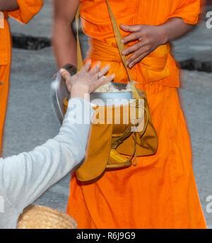 Moines en robe safran prendre l'aumône à l'aube de la population locale dans la ville de Luang Prabang, Laos, Asie du sud-est Banque D'Images