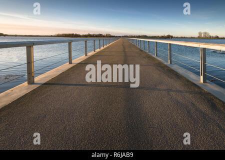 Détails d'un trottoir de béton le long du front de mer contre une digue de la rivière avec vue sur l'eau et le delta. Pont passerelle vide / fond avec co Banque D'Images