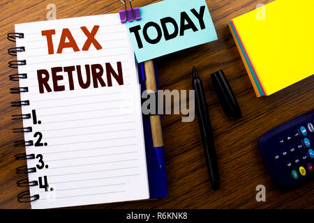 Parole, l'écriture d'impôt. Concept d'affaires Fiscalité Remboursement écrit le livre sur la note de fond en bois. Avec aujourd'hui signe. Vue de dessus de bureau. Banque D'Images