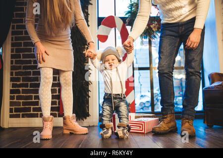 Funny little baby boy 1 ans marche apprentissage accueil en hiver dans une maison décorée de nouvelle année. Famille jeune papa et maman tenir par la main de son fils dans le loft intérieur plancher en bois près de la fenêtre