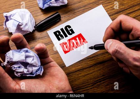 Texte de l'écriture manuscrite Big Data. Concept pour l'analyse d'affaires numérique écrit sur papier de l'ordinateur portable sur le fond en bois avec du papier plié sens penser par idée. La main de l'homme et le marqueur. Banque D'Images