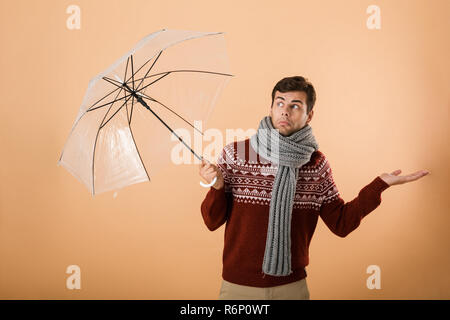 c7ce3438b6d6 ... Portrait d un jeune homme confus habillé en chandail et isolé sur fond  beige écharpe