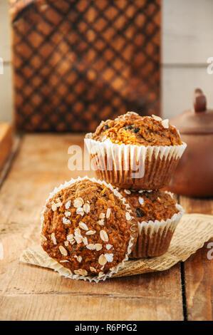 Muffins aux carottes avec les noix, les raisins et l'avoine sur un fond de bois. Style rustique. Banque D'Images