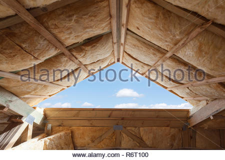 L'isolant en fibre de verre installés dans le plafond en pente d'une nouvelle maison. Banque D'Images
