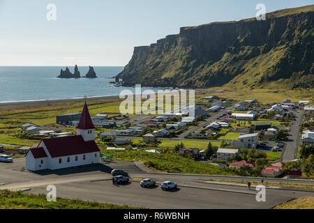 La ville islandaise de Vik dans le sud de l'Islande sur une journée ensoleillée face à la mer avec les colonnes de roche de Reynisdrangar Banque D'Images