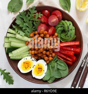 Bol Bouddha, une alimentation saine et équilibrée. Pois chiches frits, tomates cerises, concombres, poivrons, oeufs, Épinards, roquette Banque D'Images