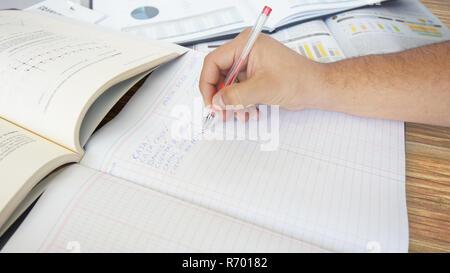 Approche d'une main humaine écrit: banques, comptes clients, comptes fournisseurs dans un grand livre sur table en bois Banque D'Images
