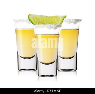 Trois verres de tequila dorée avec sel et citron vert isolé sur fond blanc. Forte boisson alcoolisée traditionnelle mexicaine. Banque D'Images