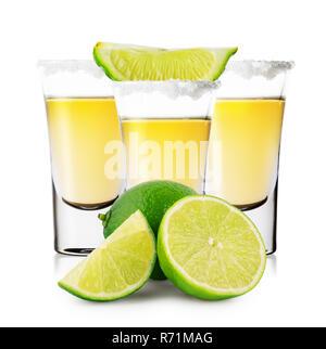 Trois verres de tequila dorée avec son ensemble et les tranches de citron vert isolé sur fond blanc. Forte boisson alcoolisée traditionnelle mexicaine. Banque D'Images