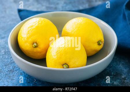 Close up de trois citrons jaunes mûrs dans un bol gris sur un fond noir en bleu. Banque D'Images