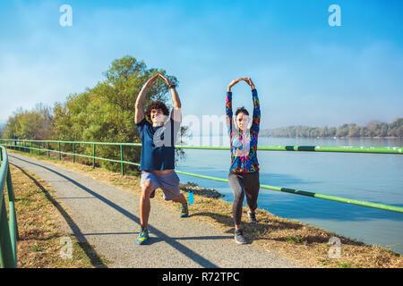 Remise en forme les jeunes l'homme et la femme s'étend dans le parc. Jeune couple de préchauffage en matinée.