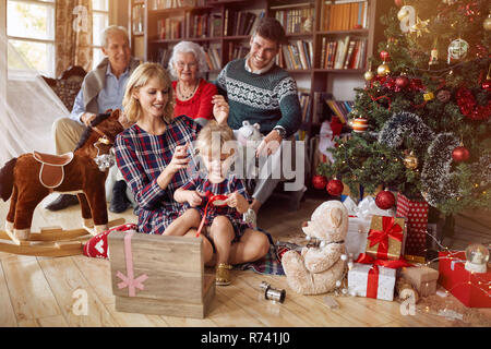 Portrait de famille Noël - famille heureuse en face de beaux arbres de Noël Banque D'Images
