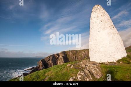 Un cairn de pierre blanchis à la chaux se trouve sur la côte de Pembrokeshire clifftops sur marquant l'entrée du port de Porthgain. Banque D'Images