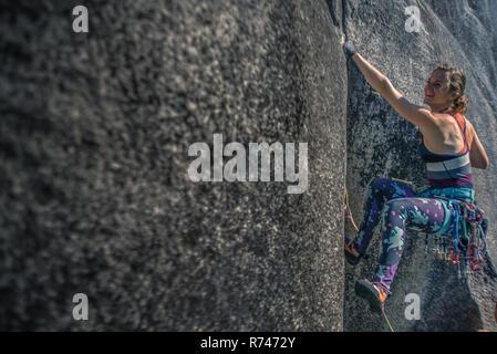 Jeune femme climber climbing rock face à la fumée, Bluffs, Squamish, British Columbia, Canada Banque D'Images