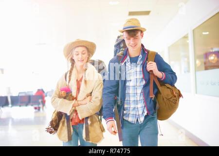 Jeune couple à l'aéroport, portant des sacs à dos, de partir en voyage Banque D'Images