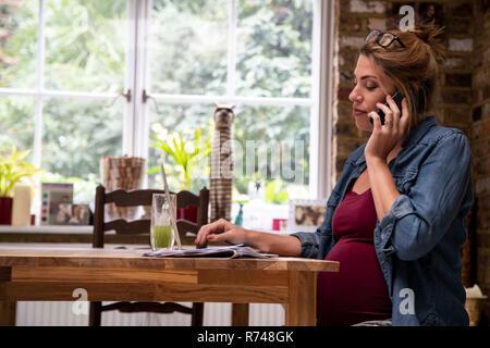 Enceinte Mid adult woman in kitchen appel smartphone Banque D'Images