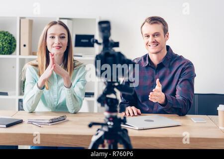 L'enregistrement vidéo sourire blogueurs vlog en face du bureau de l'appareil photo